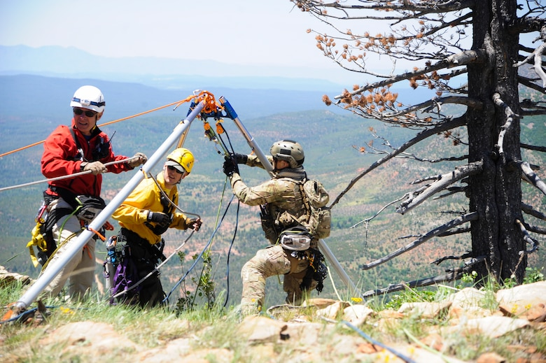 Members of several interagency search and rescue teams and a 306th Rescue Squadron reserve pararescueman connect ropes to an Arizona Vortex Tripod during Angel Thunder 2015 high angle rescue training at Mongollon Rim, Ariz., June 3, 2015. Angel Thunder is the largest personnel recovery exercise in the world combining joint, coalition and interagency personnel. Participants will train through the full spectrum of personnel recovery capabilities with numerous types of aircraft. (U.S. Air Force photo by Senior Airman Betty R. Chevalier/Released)