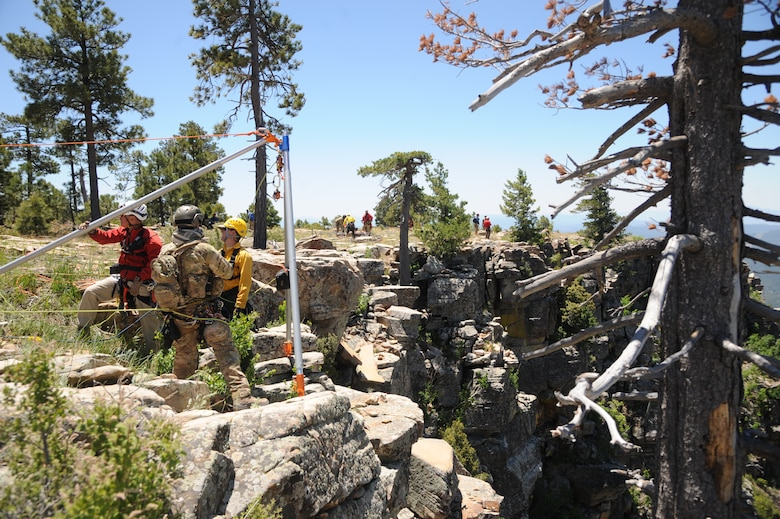 Members of several interagency search and rescue teams and a 306th Rescue Squadron reserve pararescueman connect ropes to an Arizona Vortex Tripod during Angel Thunder 2015 high angle rescue training at Mongollon Rim, Ariz., June 3, 2015. Angel Thunder is the world's largest personnel recovery exercise, hosting 11 partner nations and nine interagencies at Davis-Monthan Air Force Base, Ariz. (U.S. Air Force photo by Senior Airman Betty R. Chevalier/Released)