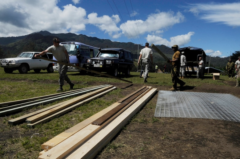 U.S. military, Papua New Guinea Defence Force and New Zealand Army members unload supplies to renovate Gahuku Primary School during Pacific Angel 15-4 in the Eastern Highlands Providence, Papua New Guinea, June 2, 2015. Pacific Angel is a U.S Pacific Command multilateral humanitarian assistance civil military operation, which improves military-to-military partnerships in the Pacific while also providing medical health outreach, civic engineering projects and subject matter exchanges among partner forces. (U.S. Air Force photo by Staff Sgt. Marcus Morris/Released)
