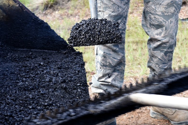 Members of the 341st Civil Engineer Squadron pavement and equipment section place hot-mix asphalt to repair defective pavement on Perimeter Road on Malmstrom Air Force Base, Mont., June 3, 2015. Road repair construction maintains 34.6 miles of road, 158.3 acres of paved parking lots, and 13.9 miles of sidewalks. (U.S. Air Force photo/Chris Willis)