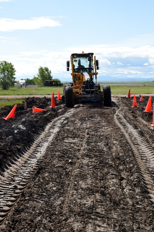 Master Sgt. Ronald Hertz, 341st Civil Engineer Squadron pavement and equipment, operates a grader to allow access to a road for a helicopter tactical slide area project June 3, 2015, at Malmstrom Air Force Base, Mont. The helicopter tactical slide area construction will create an area for the 40th Helicopter Squadron to practice skid landings in the event of an emergency. (U.S. Air Force photo/Chris Willis)