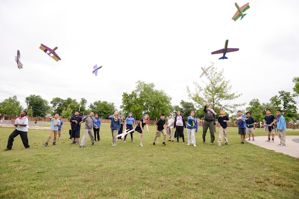 Maj. Donna Mae Williams, a pilot assigned to the 465th Air Refueling Squadron at Tinker Air Force Base, Okla., throws Styrofoam airplanes with 4th grade students from Kendall-Whittier Elementary School on May 20 in Tulsa, Okla. Williams visited the students after corresponding with them about her battle with cancer and career as a pilot in the Air Force Reserve. (Air Force photo by Staff Sgt. Caleb Wanzer/Released)