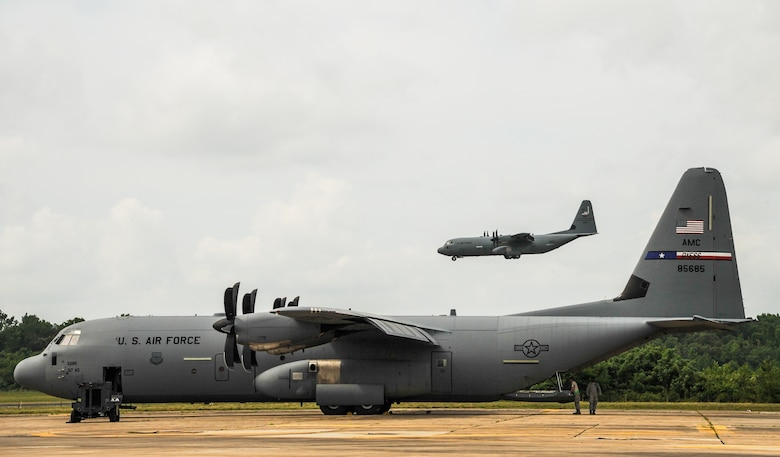 A C-130J prepares to land as a parked C-130J is prepped for departure May 20, 2015, at Little Rock Air Force Base, Ark. The C-130 is one of the most versatile cargo delivery aircraft in the Air Force for its airdrop and air-land mission capabilities (U.S. Air Force photo by Senior Airman Harry Brexel)