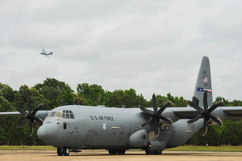 A C-130J prepares to land as another C-130J on the ground prepares for departure May 20, 2015, at Little Rock Air Force Base, Ark. The C-130 is one of the most versatile cargo delivery aircraft in the U.S. Air Force for its airdrop and air-land mission capabilities (U.S. Air Force photo by Senior Airman Harry Brexel)