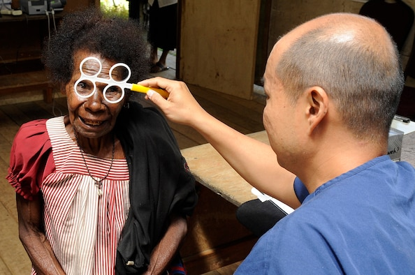 Lt. Col. Weilun Hsu, the 374th Aerospace Medicine Squadron optometry flight commander from Yokota Air Base, Japan, determines which glasses to prescribe a local during Pacific Angel 15-4 at Unggai Primary School in Papua New Guinea, June 1, 2015. The optometrists prescribed more than 200 glasses, allowing the locals to walk away seeing better than before. (U.S. Air Force photo/Staff Sgt. Marcus Morris)