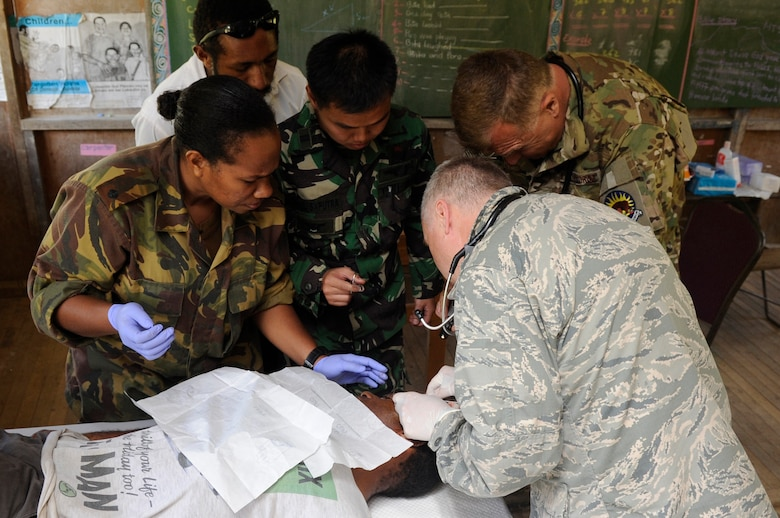 Lt. Col. Jeffrey Freeland, the Pacific Air Forces chief of aerospace medicine from Joint Base Pearl Harbor-Hickam, Hawaii, removes a fatty tumor from a local man's head while medical professionals from Papua New Guinea, Indonesia and the U.S. Air National Guard assist during Pacific Angel 15-4 at Unggai Primary School in Papua New Guinea, June 1, 2015. The medical team treated 514 patients by the end of their first day and reached a total of 2,000 patients treated in their three-day stay at their first health services outreach location. The mission of PACANGEL is to upgrade education and health facilities in the area, as well as, work to deepen local disaster response capabilities. (U.S. Air Force photo/Staff Sgt. Marcus Morris)
