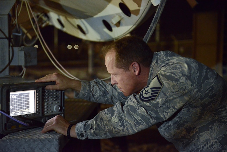 Master Sgt. Brian Popham, 379th Expeditionary Operations Support Squadron Silent Sentry, monitors and adjusts signal strength from an antenna during routine maintenance checks signal May 27, 2015 at Al Udeid Air Base, Qatar. The Silent Sentry team monitors high priority satellite communication signals, detects electromagnetic interference on those signals and geolocates the source of that interference along with other signals of interest. (U.S. Air Force photo/Staff Sgt. Alexandre Montes)