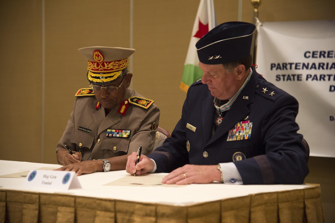 Maj. Gen. Zakaria Cheik Ibrahim, the Djiboutian Armed Forces (FAD) chief of defense, and Maj. Gen. Edward Tonini, the Kentucky National Guard (KNG) adjutant general, sign a State Partnership Program agreement at the Kempinski Hotel, Djibouti, June 2, 2015. The agreement means a long-term cooperative agreement between the KNG and FAD that will foster mutually beneficial exchanges between the two at all levels of the military as well as the civilian world. (U.S. Air Force photo/Staff Sgt. Nathan Maysonet)