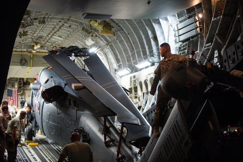 Airmen assigned to the 8th Airlift Squadron and the 41st Expeditionary Rescue Squadron offload an HH-60G Pave Hawk from a C-17 Globemaster III at Bagram Airfield, Afghanistan, May 27, 2015. Air Force cargo aircraft have delivered 19,900 short tons of cargo throughout Afghanistan this year. (U.S. Air Force photo/Tech. Sgt. Joseph Swafford)