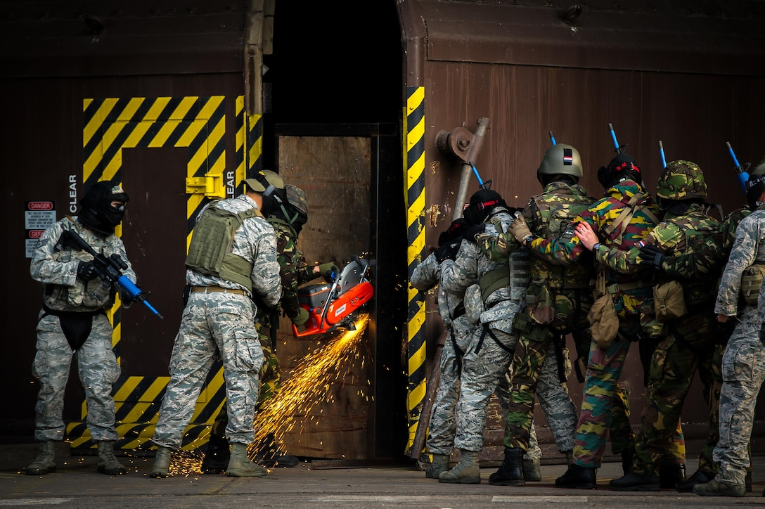U.S. and European security forces breach a hardened facility during a combat training course on Ramstein Air Base, Germany, May 30, 2015. The Battlefield Leaders Assaulter Course, Integrated Combat Essentials is designed to teach security forces members from multiple countries advanced tactics and shooting skills for use in the event of a base security breach. (U.S. Air Force photo/Tech. Sgt. Ryan Crane)