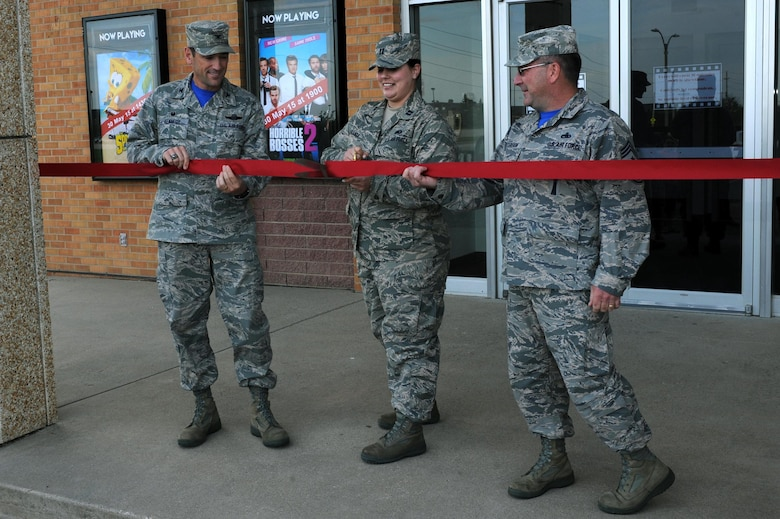 Col. Kevin Kennedy (left), 28th Bomb Wing commander, Capt. Kristen Miranda (middle), 28th Force Support Squadron executive officer, and Chief Master Sgt. Kevin Peterson (right), 28th BW command chief, cut the ribbon at the Base Theater Grand Opening at Ellsworth Air Force Base, S.D., May 29, 2015. The theater shows two free movies each week and sells concessions sponsored by both the 28th FSS and private organizations which can be paid for in cash. (U.S. Air Force photo by Senior Airman Hailey R. Staker/Released)