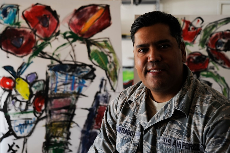 Master Sgt. Enrique Santiago, 30th Force Support Squadron career assistance supervisor, sits in front of two of his paintings at his garage-studio June 5, 2015, Vandenberg Air Force Base, Calif. Santiago is an avid practitioner of abstract expressionism and recently had several paintings placed in a gallery in Los Alamos. (U.S. Air Force photo by Airman 1st Class Ian Dudley/Released)