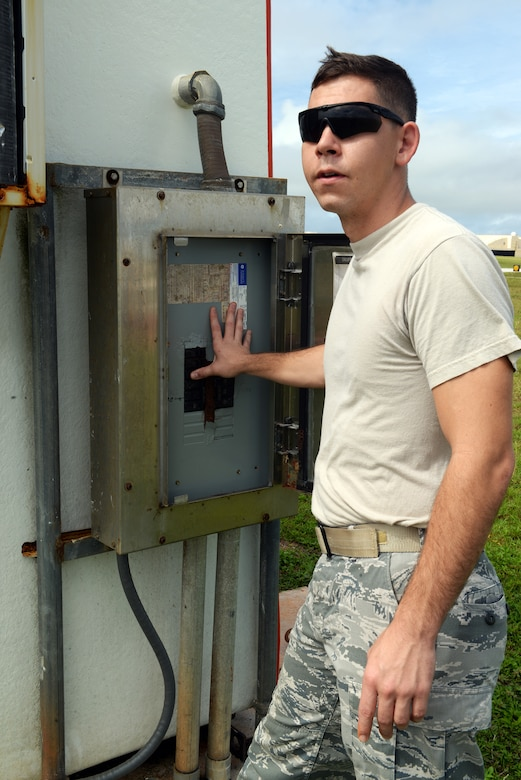 Senior Airman Patrick Duffie, 36th Operations Support Squadron airfield systems technician, flips breaker switches to ensure power is being properly dispersed to the wind bird, a wind sensor, June 2, 2015, at Andersen Air Force Base, Guam. The technicians guarantee safe landings everyday by performing routine checks on essential equipment such as the glideslope, localizer, and TACAN or tactical air navigation. (U.S. Air Force photo by Senior Airman Amanda Morris/Released)
