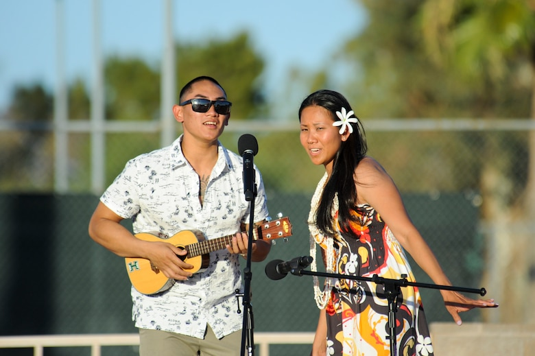 U.S. Air Force Senior Airman Lutgardo Baltazar, 612th Air & Space Operations Center, plays a ukulele and sings with Tech. Sgt. Mariefaye McGuire, 355th Medical Support Squadron, while they emcee the Asian American & Pacific Islander Heritage Month luau at Davis-Monthan Air Force Base, Ariz., May 29, 2015.  The luau also featured live performances by dancers, drummers and martial artists.  (U.S. Air Force Photo by Airman 1st Class Chris Massey/Released)