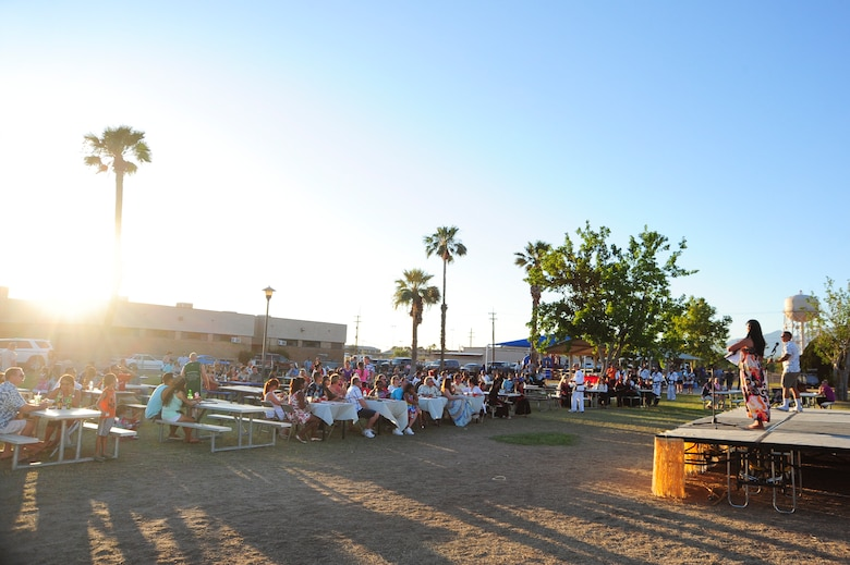 Attendees of the Asian American & Pacific Islander Heritage Month luau listen to the event?s emcees at Davis-Monthan Air Force Base, Ariz., May 29, 2015.  The annual event featured displays, performances and cuisine showcasing the cultures and traditions of various Asian and Pacific regions.  (U.S. Air Force Photo by Airman 1st Class Chris Massey/Released)