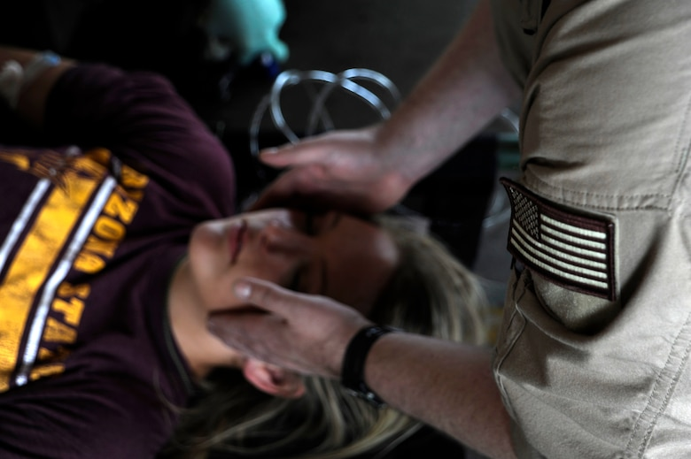 U.S. Air Force Tech. Sgt. Clifford Knesel, 187th Aeromedical Evacuation Squadron medical technician, stabilizes the head of a simulated flood victim with internal bleeding during an Angel Thunder 2015 mass casualty exercise at Winslow-Lindbergh Regional Airport, Ariz., June 5, 2015. Service members, University of Arizona and Northern Arizona University students acted as simulated patients to create a realistic experience during the exercise. (U.S. Air Force photo/Tech. Sgt. Courtney Richardson/Released)