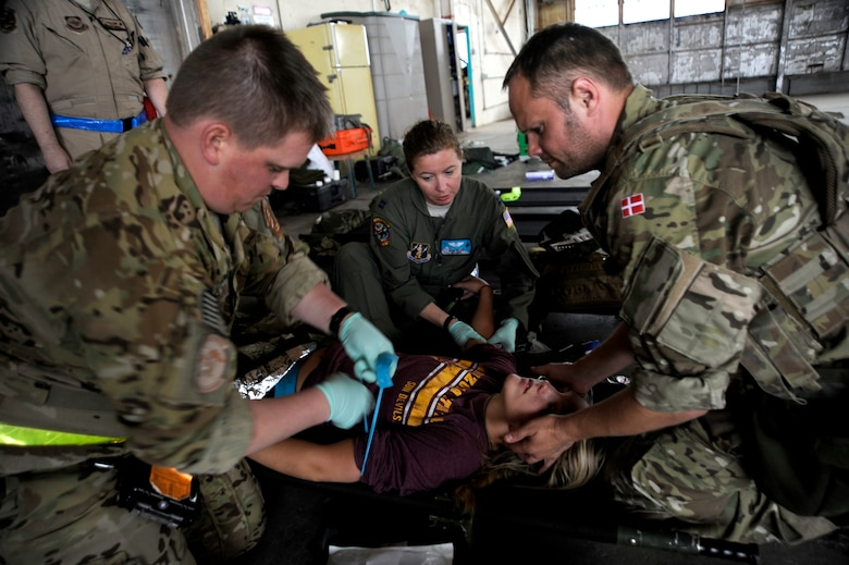 U.S. Air Force Airmen and a Royal Danish Air Force rescue member work together to treat a simulated flood victim with internal bleeding during an Angel Thunder 2015 mass casualty exercise at Winslow-Lindbergh Regional Airport, Ariz., June 5, 2015. Service members, University of Arizona and Northern Arizona University students acted as simulated patients to create a realistic experience during the exercise. (U.S. Air Force photo/Tech. Sgt. Courtney Richardson/Released)