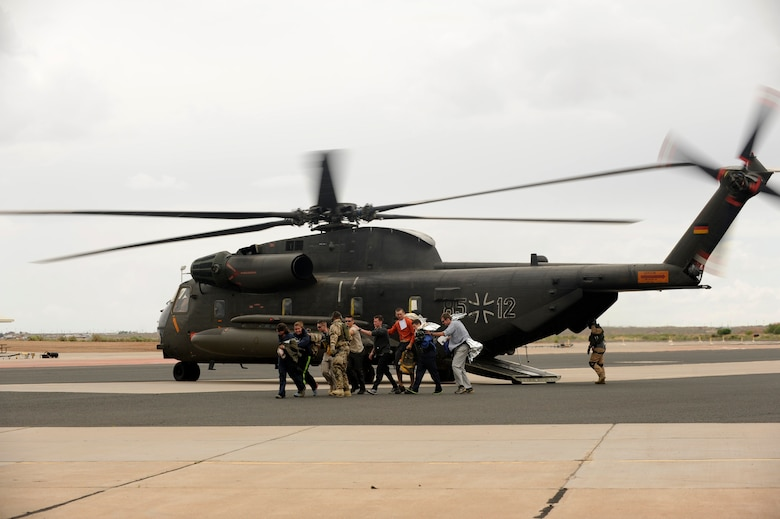 Simulated flood victims are escorted from a German Air Force Air Force CH-53GS helicopter during an Angel Thunder 2015 mass casualty exercise at Winslow-Lindbergh Regional Airport, Ariz., June 5, 2015. U.S. military forces and partner-nations worked together during the exercise to transport simulated patients from Camp Navajo Training Site to the casualty collection point located at the Winslow-Lindbergh Regional Airport. (U.S. Air Force photo/Tech. Sgt. Courtney Richardson/Released)