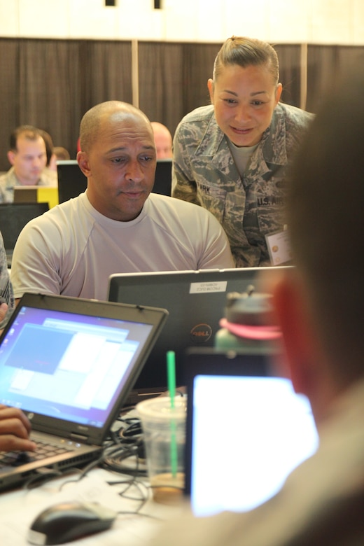 Senior Airman Jasper Green, from the 292nd Combat Communications Squadron, and Master Sgt. Misty Park, from the 209 Air Operations Group, Hawaii Air National Guard, attempt to resolve a cyber attack during the Po'oihe 2015 Cyber Security Exercise at the University of Hawaii Manoa Campus Center Ballroom on June 4, 2015. The exercise is designed to provide a controlled learning environment to support collaboration and education amongst all participants. (U.S. Air National Guard photo by Airman 1st Class Robert Cabuco)