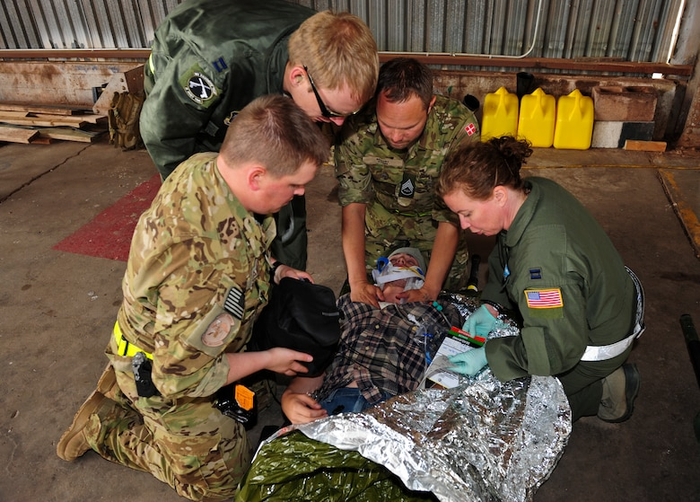 U.S. Air Force and Royal Danish Air Force medical personnel treat a simulated victim for neck and head injuries during an Angel Thunder 2015 mass casualty exercise at Winslow-Lindbergh Regional Airport, Ariz., June 5, 2015. Service members, University of Arizona and Northern Arizona University students acted as simulated patients to create a realistic experience during the exercise. (U.S. Air Force photo by Airman 1st Class Chris Drzazgowski/Released)