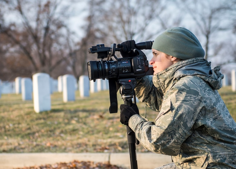 Staff Sgt. Nikoletta Kanakis, a Massachusetts Air National Guard broadcaster deployed to Air Force Mortuary Affairs Operations at Dover Air Force Base, Del., captures video footage during a wreath laying event at Arlington National Cemetery, Dec. 13, 2014. Kanakis' primary duty is to document the dignified transfer of human remains to be provided to families of the fallen. (U.S. Air Force photo by Captain Raymond Geoffroy/Released)