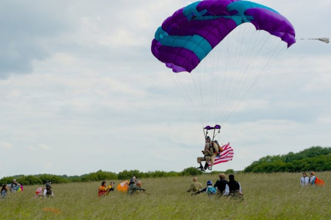 """James """"Pee Wee"""" Martin approaches for a final landing near Utah Beach, France, with tandem jump partner Dominic Kervestin, June 5, 2014. Martin is 93, and has completed a final parachute jump on the occasion of the 70th anniversary of the D-Day invasion of occupied France. (Photo by Senior Airman Alexander W. Riedel)"""