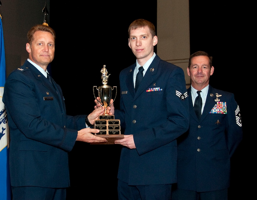 JOINT BASE ELMENDORF RICHARDSON, Alaska -- Senior Airman Brooklyn Panfil, a member of the Alaska Air National Guard's 176th Medical Group, receives the 176th Wing Airman of the Year Award at the wing's annual awards ceremony here June 7, 2015. National Guard photo by Tech. Sgt. Alicia N. Halla.