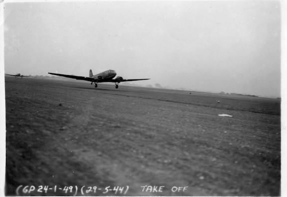 "A C-47 Skytrain with the tail number 857, takes off from Upottery Airfield, in East Devon, England, May 29, 1944. At this point, it had not received its invasion strips. The ""D8"" on the fuselage tells that it was a plane assigned to the 94th Troop Carrier Squadron. The ""B"" on the tail is its individual marker. This aircraft is now a static display of the 176th Wing on JBER, Alaska."