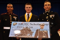 Pierce Gilman, a recent graduate of Trinity High School in Manchester, New Hampshire, receives an $180,000 Naval Reserve Officer Training Corps, Marine Corps Option, scholarship from Capt. Zachary Johnson (right) and Sgt. Alex Figueroa during the school's awards ceremony May 27, 2015, at the school. Capt. Johnson is the executive officer of Recruiting Station Portsmouth, NH, and Sgt. Figueroa is a canvassing recruiter for Recruiting Substation Manchester, NH.