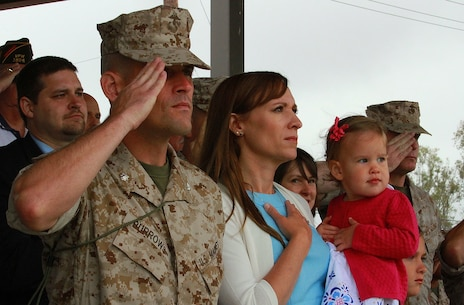 Lieutenant Col. Damon K. Burrows, the newly-appointed commanding officer of 9th Communication Battalion, I Marine Expeditionary Force Headquarters Group, and his family render honors to the national colors during a change of command ceremony aboard Marine Corps Base Camp Pendleton, Calif., June 4, 2015. Burrows most recently served as the assistant chief of staff, G-6, for the 1st Marine Logistics Group, I MEF, and said he plans to increase the battalion's cyber operations presence and effectiveness. (U.S. Marine Corps photo by Lance Cpl. Caitlin Bevel)