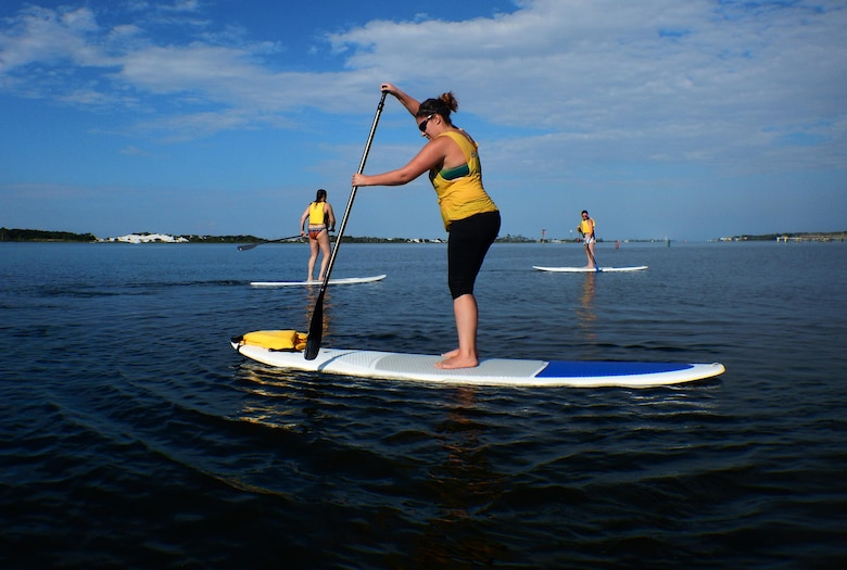 Sara Francis, Kirsten J. Nunweiler and Stephany Pippin, assigned to the 1st Special Operations Force Support Squadron, paddle in the Santa Rosa Sound during a stand up paddle boarding class at Hurlburt Field, Fla., June 4, 2015. The Outdoor Recreation SUP class is new to Hurlburt Field this year and classes are held Tuesdays and Thursdays from 7:30 a.m. to 8:30 a.m. weekly at the Sound Side. (U.S. Air Force photo/Airman Kai White)
