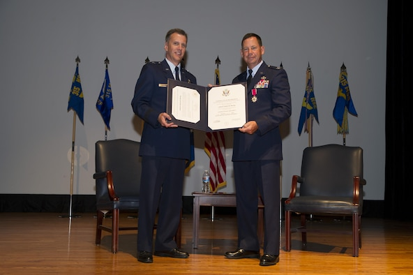 Brig. Gen. Randall A. Ogden presents a certificate of retirement to Col. James B. Hurley June 7, 2015 at the Joint Base Charleston theater in Charleston, S.C. During his 33-33-year career, Hurley first served with the active duty Air Force before transitioning to the Air Force Reserve. Hurley donned the Air Force uniform for the last time but will go on to serve in a civilian capacity with the 628th Air Base Wing Mission Support Group at the base. Hurley was the 315th Mission Support Group commander at Joint Base Charleston, and Ogden is the Director, Air Force Reserve Plans, Programs and Requirements, Headquarters U.S. Air Force. (U.S. Air Force Photo by Tech. Sgt. Shane Ellis)