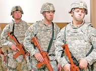 From left, Sgt. Devin McClain, of 2nd Battalion, 70th Armor Regiment, 2nd Armored Brigade Combat Team, 1st Infantry Division; Sgt. Guertin; Pfc. Jonathan Munas, 4th Squadron, 4th Cavalry Regiment, 1st Armored Brigade Combat Team, 1st Inf. Div., wait to enter a room. They and four other Soldiers and NCOs in the competition were required to subdue an attacker at close quarters using combatives training.