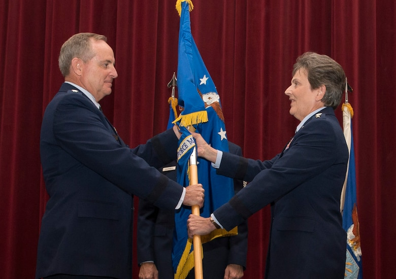 In the time-honored military tradition signifying assumption of command, Air Force Chief of Staff Gen. Mark. A. Welsh III passes the Air Force Materiel Command guidon, or unit flag, to Gen. Ellen Pawlikowski. Pawlikowski assumed command of AFMC Jun. 8, 2015, in a ceremony at the Air Force Institute of Technology's Kenney Auditorium. (U.S. Air Force photo/Wes Farnsworth)