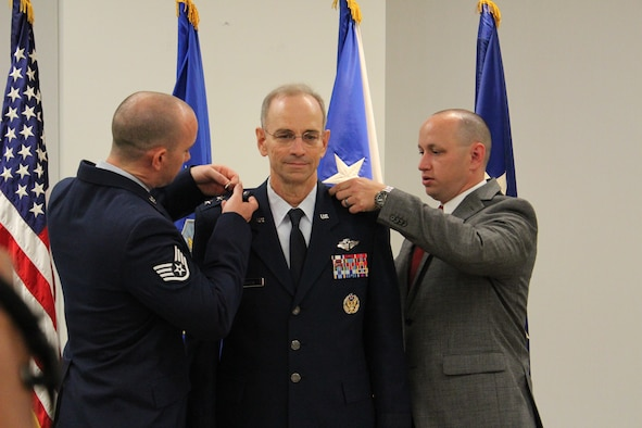 Staff Sergeant Ross Ediger, left, and Zachery Ediger, pin the third star on their father, Lt. Gen. Mark Ediger during the promotion ceremony June 8 at the Defense Health Headquarters, Falls Church, Va. General Ediger became the 22nd Air Force Surgeon General during the ceremony, officiated by Vice Chief of Staff Gen. Larry O. Spencer.  (U.S. Air Force photo by Jonathan Stock.)