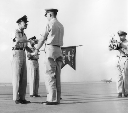 The guidon for the Headquarters Squadron, 3595th Flying Training Group can be seen during a ceremony on the flightline at Nellis Air Force Base, Nev., in 1956. Today's guidon traces its heritage back to smaller flags used by cavalry units in Europe during the late 1700s and early 1800s; these were used by squadrons within a larger regimental formation both on the battle field and in camps. (Courtesy photo)