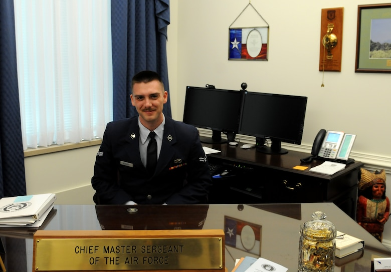 Airman 1st Class Duncan McElroy, 81st Training Wing Public Affairs photojournalist, sits behind Chief Master Sgt. of the Air Force James Cody's desk during a Capitol Hill visit, May 14, 2015, at the Pentagon. McElroy was selected to accompany base leadership on the trip, which was meant to foster partnerships between Air Force and state congressional representatives. (Courtesy photo)