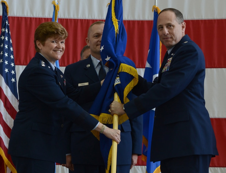 Gen. Janet Wolfenbarger, Air Force Materiel Command commander, passes the guidon to Lt. Gen. Lee Levy II during the Air Force Sustainment Center change of command ceremony Friday at Tinker Air Force Base. Chief Master Sgt.  Jason France, AFSC command chief, stands ready to receive the ceremonial guidon from the new commander.  Lt. Gen. Levy succeeds Lt. Gen. Bruce Litchfield, who will retire after 34 years of military service. As the AFSC commander, Lt. Gen. Levy is responsible for operations which span three air logistics complexes, three air base wings, two supply chain management wings, and multiple remote operating locations, incorporating more than 35,000 military and civilian personnel. In addition, he oversees installation support to more than 75,000 personnel working in 140 associate units at the three AFSC bases.