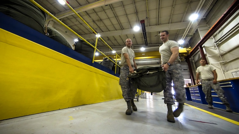 Technical Sgt. Jesse Sorrell (left) and Technical Sgt. Joshua Ellis carry a G-12E Type V platform parachute after recovering it from the dropzone on June 6, 2015 to store it for the next training air drop. The Airman from the 182d Airlift Wing, Small Air Terminal, Peoria, Ill., check and repack the parachute after it was used in a recent C-130 air drop training mission with heavy equipment at the dropzone. (U.S. Air National Guard photo by Master Sgt. Scott Thompson/Released)