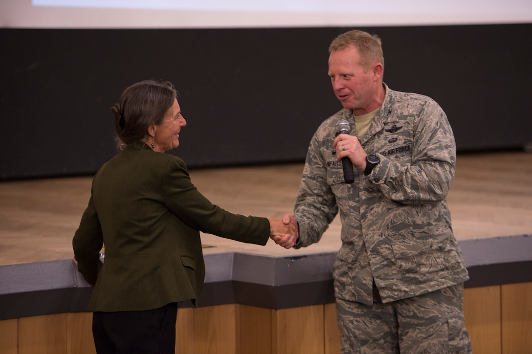 U.S. Air Force Col. Joe McFall, 52nd Fighter Wing commander, presents a coin to retired U.S. Army Brig. Gen. Rhanda Cornum, a Department of Defense resiliency consultant, at the base theater on Spangdahlem Air Base, Germany, June 4, 2015, during the 52nd Fighter Wing's Resiliency Day. McFall thanked Cornum for being the key speaker kicking off the base's resiliency themed events for the day. (U.S. Air Force photo by Staff Sgt. Christopher Ruano/Released)