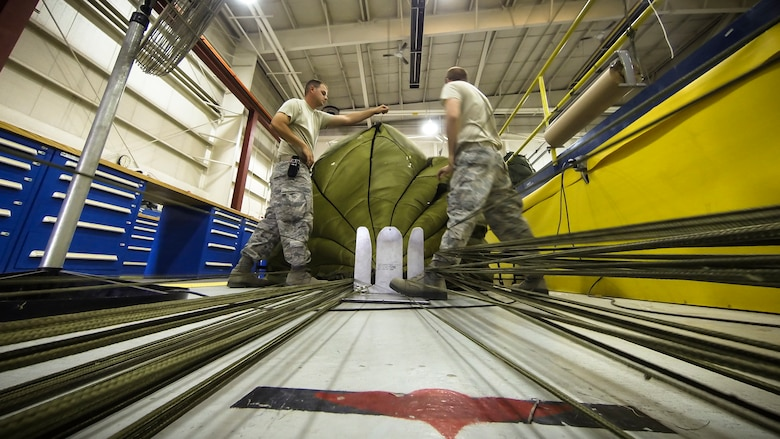 Technical Sgt. Jesse Sorrell (right) and Technical Sgt. Jeremy Martinson (left) untagle parachute cord on a G-12E Type V platform parachute after recovering it from the dropzone on June 6, 2015. The Airman from the 182d Airlift Wing, Small Air Terminal, Peoria, Ill. check and repack the parachute after it was used in a recent C-130 air drop training mission with heavy equipment at the dropzone. (U.S. Air National Guard photo by Master Sgt. Scott Thompson/Released)