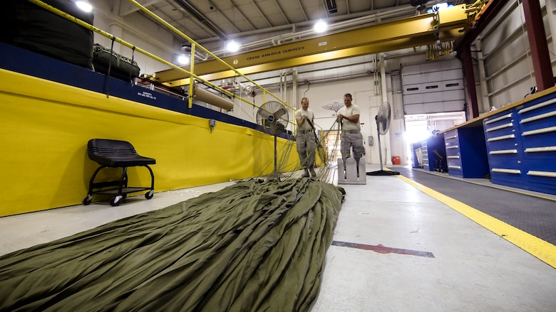 Technical Sgt. Jesse Sorrell (left) and Technical Sgt. Jeremy Martinson untagle parachute cord on a G-12E Type V platform parachute after recovering it from the dropzone on June 6, 2015. The Airman from the 182d Airlift Wing, Small Air Terminal, Peoria, Ill. check and repack the parachute after it was used in a recent C-130 air drop training mission with heavy equipment at the dropzone. (U.S. Air National Guard photo by Master Sgt. Scott Thompson/Released)