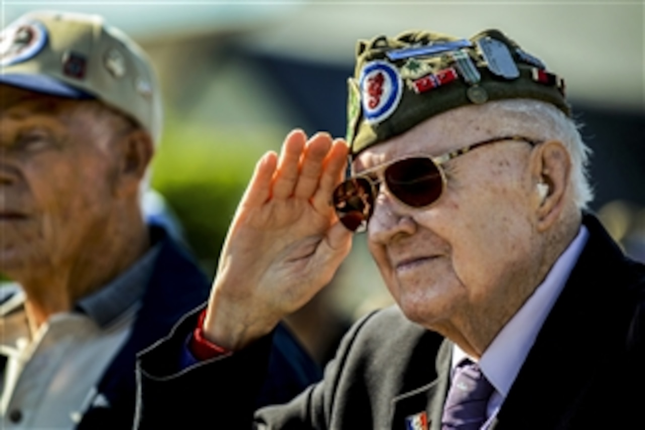 "A World War II veteran salutes as ""The Star-Spangled Banner"" plays during a D-Day ceremony at the 9th Air Force Memorial in Picauville, France, June 4, 2015."