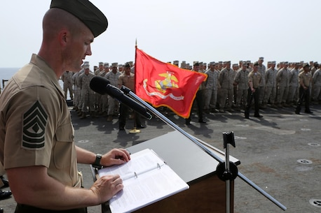 First Sgt. John Beckett, the company first sergeant for Kilo Company, Battalion Landing Team 3rd Battalion, 6th Marine Regiment, 24th Marine Expeditionary Unit, gives a speech during the Battle of Midway ceremony aboard the dock landing ship USS Fort McHenry (LSD 43), June 6, 2015. The 24th MEU is embarked on the ships of the Iwo Jima Amphibious Ready Group and deployed to maintain regional security in the U.S. 5th Fleet area of operations. (U.S. Marine Corps photo by Sgt. Devin Nichols)
