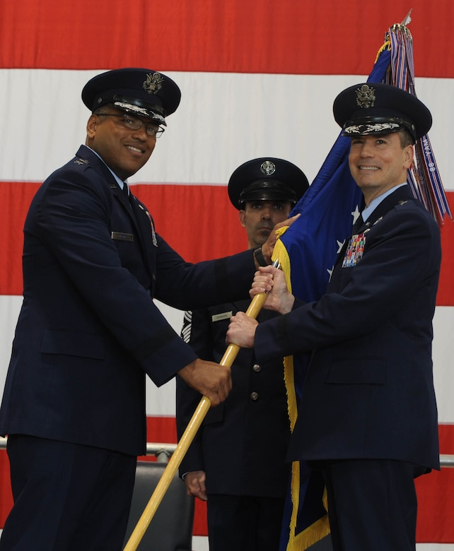 Maj. Gen. Richard Clark, the Eighth Air Force commander, hands over the wing guidon to Brig. Gen. Paul W. Tibbets IV, the 509th Bomb Wing commander, during a change of command ceremony at Whiteman Air Force Base, Mo., June 5, 2015. The presentation of the guidon to Tibbets symbolized the official change of command from the old commander to the new commander. (U.S. Air Force photo/Staff Sgt. Alexandra M. Longfellow)
