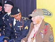 "Sgt. Fidel Cruz, chemical, biological, explosive, radiological and nuclear noncommissioned officer, HHC, 101st BSB, 1st ABCT, 1st Inf., Div., talks with D-Day veteran, retired 1st Sgt. Joseph Crandall, a former ""Big Red One"" Soldier, during the NASCAR Troops to the Track event May 9 at the Kansas Speedway."
