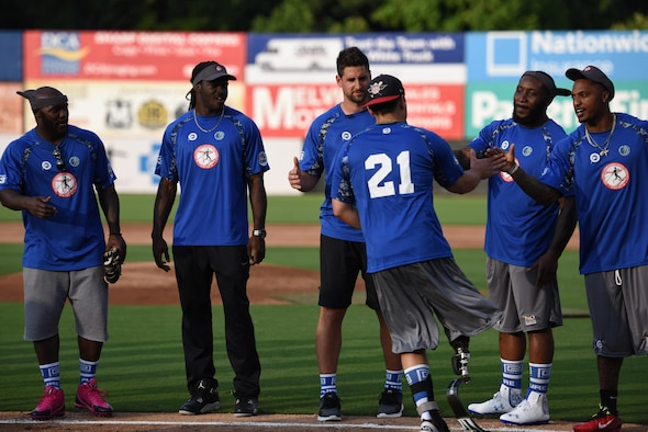Mike Dreyer, Wounded Warrior Amputee Softball Team, representing the Air Force, shakes hands with his team members during team introductions at the 3rd annual Amputee Warrior Softball Classic June 6, 2015, at Prince George's Stadium in Bowie, Md. (U.S. Air Force Photo/Staff Sgt. Carlin Leslie)