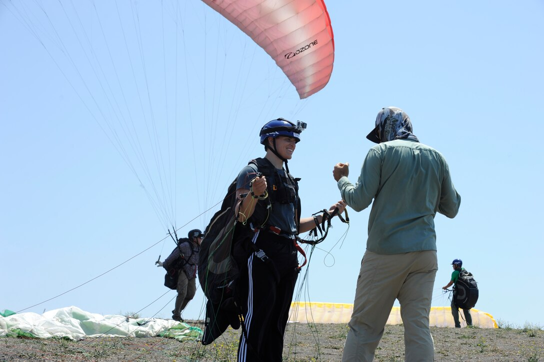 Airman 1st Class Joseph Weiler, 30th Medical Operations Squadron aerospace medical technician, receives pre-flight instructions from Kevin Howe, paragliding instructor, June 6, 2015, Santa Barbara, Calif. Vandenberg's Outdoor Recreation features the Single Airman Initiative, a program that enables Airmen to participate in diverse and adventurous events year-round. (U.S. Air Force Photo by Airman 1st Class Robert J. Volio/Released)