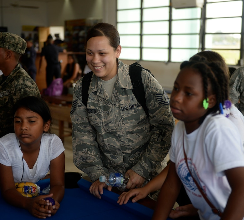 U.S. Tech. Sgt. Tiffany Rewerts, 87th Medical Operations Squadron medical technician, 87th Medical Group, out of Joint Base McGuire-Dix-Lakehurst, N.J., and Abilene, Texas native, spends time playing with children during the Guardians of the Fatherland event at Puerto Castillo Naval Base in Trujillo, Honduras, June 6, 2015. The event was attended my more than 20 NEW HORIZONS Honduras 2015 volunteers. NEW HORIZONS was launched in the 1980s and is an annual joint humanitarian assistance exercise that U.S. Southern Command conducts with a partner nation in Central America, South America or the Caribbean. The exercise improves joint training readiness of U.S. and partner nation civil engineers, medical professionals and support personnel through humanitarian assistance activities. (U.S. Air Force photo by Capt. David J. Murphy/Released)