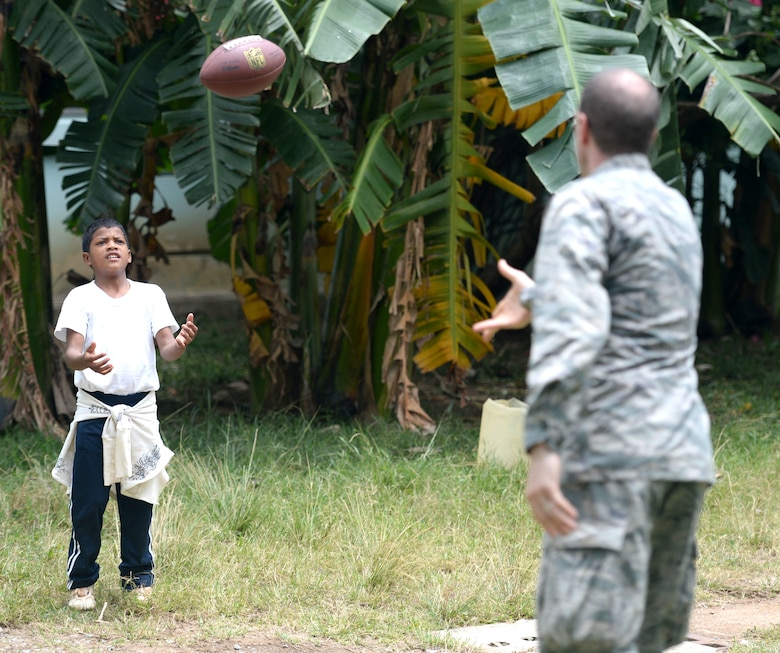 U.S. Maj. Norman Zellers, 60th Medical Operations Squadron, 60th Medical Group physician assistant, out of Travis Air Force Base, Calif., and Allentown, Pa., tosses a football to Lucas Arellano Paz, 13, during the Guardians of the Fatherland event at Puerto Castillo Naval Base in Trujillo, Honduras, June 6, 2015. More than 20 NEW HORIZONS Honduras 2015 personnel volunteered to participate in the event. NEW HORIZONS was launched in the 1980s and is an annual joint humanitarian assistance exercise that U.S. Southern Command conducts with a partner nation in Central America, South America or the Caribbean. The exercise improves joint training readiness of U.S. and partner nation civil engineers, medical professionals and support personnel through humanitarian assistance activities. (U.S. Air Force photo by Capt. David J. Murphy/Released)